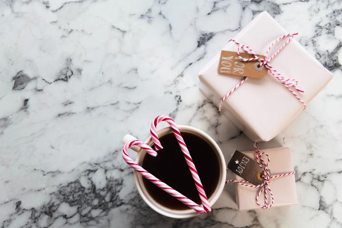 white ceramic mug beside gift boxes